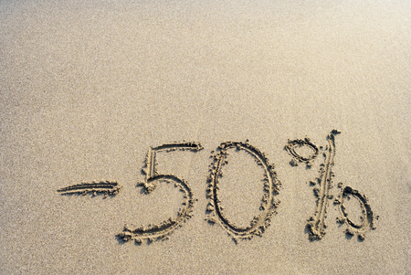 inscription on the sand minus fifty percent, -50 %,