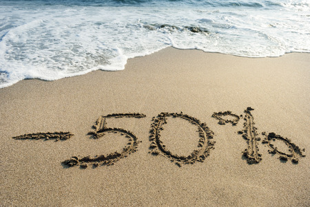 inscription on the sand minus fifty percent, - 50 %, sea wave on the sand with the inscription fifty