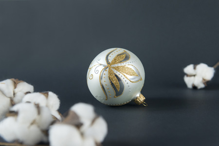 1 silver Christmas ball with Golden pattern, cotton branches on black background, Christmas decor Reklamní fotografie - 110850901