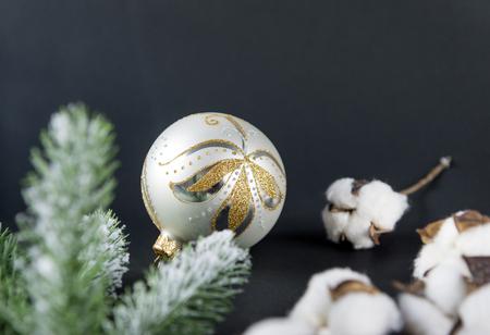 1 silver Christmas ball with Golden pattern, cotton branches, spruce branch on black background, Christmas decor Reklamní fotografie - 110850902