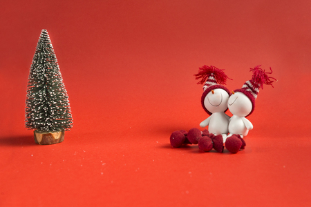 artificial, green spruce, 2 toy snowmen on red background, Christmas decor 免版税图像