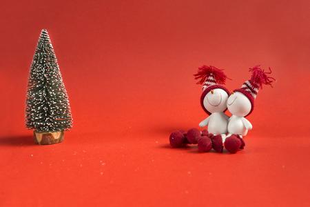 artificial, green spruce, 2 toy snowmen on red background, Christmas decor 版權商用圖片