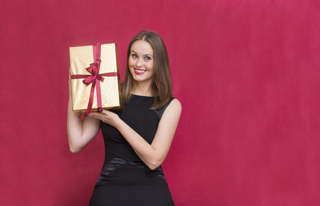 1 white girl holding a Golden box in a gift box on a red background, a girl rejoices, a young woman smiles widely