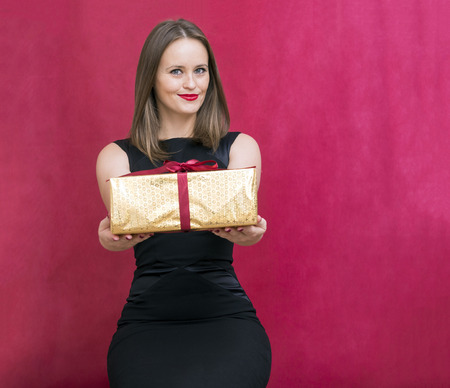 white girl with a gift in a Golden box ,a girl in a black dress with a gift on a red background, a young woman, smiling, holiday gift