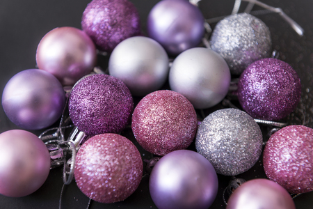 lot of silver and pink Christmas balls on a black background, Christmas decorations, top view