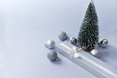 silver Christmas balls, gift box, Christmas tree on a gray background, Reklamní fotografie - 112878100