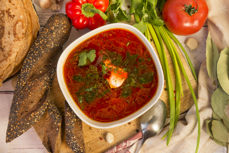 borsch with sour cream and herbs, bread, vegetables, greens, food, top view, Russian cuisine Stock Photo