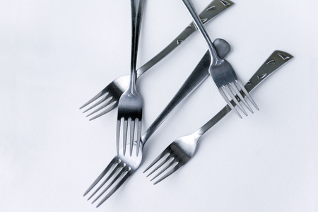 several metal forks with teeth on white background