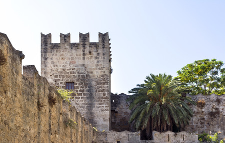 medieval stone tower and wall of  fortress on Rhodes, palm tree, sky 新聞圖片