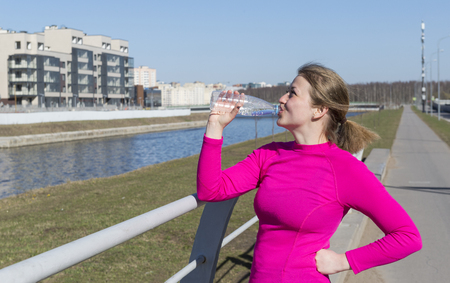 girl in pink sports top drinking water from a bottle on the canal embankment, athlete