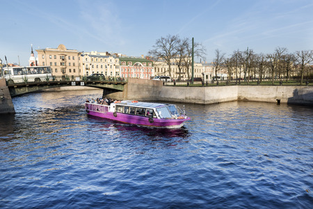 pleasure boat with tourists floating on the river in St. Petersburg, embankment, bridge, spring in the city