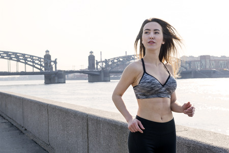 1 beautiful white athletic girl running along the river embankment on the bridge background, young woman with long hair in sports top doing sports in the outdoors  in the city Reklamní fotografie - 122678932