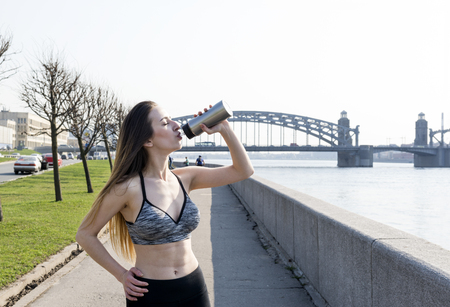 beautiful sports girl with long hair in gray sports top drinking water on the river embankment in the city on the bridge background Reklamní fotografie - 122678933