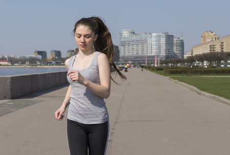 slender sports girl runs down the street on a Sunny day, a girl with long hair in sports clothes runs along the embankment of the Neva river in St. Petersburg Reklamní fotografie - 122678984
