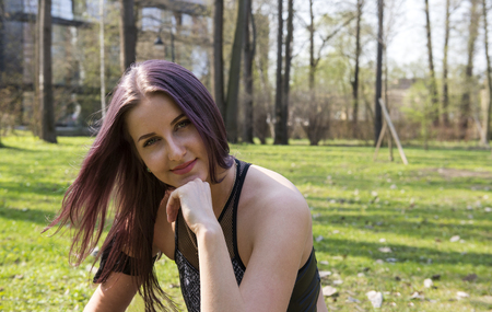 1 white beautiful girl with long hair sitting on a green glade in spring, close up portrait Reklamní fotografie - 122594253