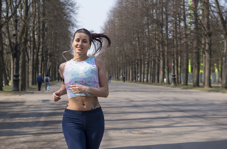 beautiful slim sporty girl running in the Park in the spring, the girl in sportswear is engaged in sports
