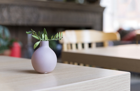 small vase with a green twig on a wooden table in a cafe, room decor