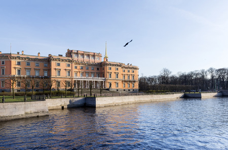 building Mikhailovsky castle in St. Petersburg on the banks of the river Moika at sunset, a bird in the sky