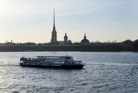 pleasure boat sailing on the Neva river in St. Petersburg opposite the Peter and Paul fortress at sunset, the building of the Orthodox Cathedral on hare island Reklamní fotografie