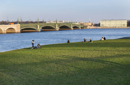 green lawn covered with grass on the banks of the Neva river in St. Petersburg ,Hare island, bridge over the river, buildings on the waterfront, people walking outdoors on a Sunny day Reklamní fotografie - 122642039