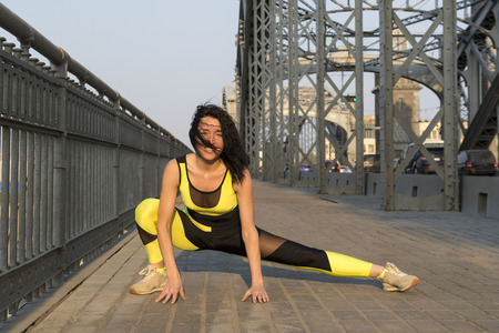 1 white girl is stretching on a bridge outdoors, sports, Stock Photo