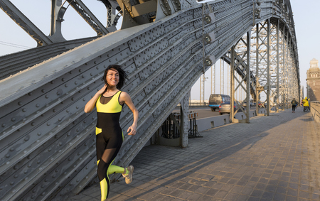 white girl runs across the metal bridge and smiling, runner Stock Photo