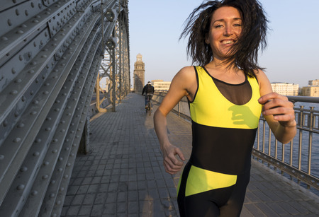 athletic girl running across the bridge at sunset and smiling , exercise outdoors Stock Photo