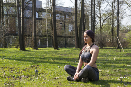 beautiful slim athletic girl in sports clothes sitting in a clearing among the greenery in the Park in the Lotus position , a young brunette woman sitting on the grass in the Park Reklamní fotografie - 122781141