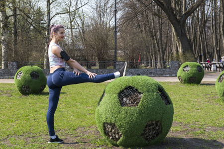 1 white girl in a tracksuit is training in the Park outdoors, girl doing stretching foot next to the ball futbolny , flowerbed