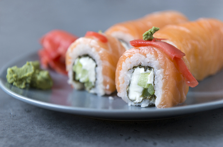 Philadelphia rolls with salmon, soft cheese and cucumber, ginger and wasabi on a grey plate on a dark background Reklamní fotografie - 122781172