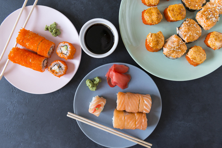 many Japanese rolls with caviar and salmon on 3 plates, cold Japanese rolls, baked hot rolls, top view, soy sauce in a bowl, sushi sticks, California rolls, Philadelphia rolls, baked rolls