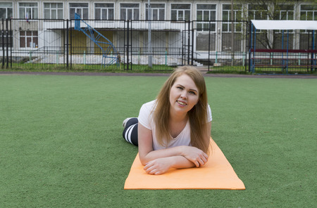 1 white girl in sports clothes lying on the Mat on the artificial grass on the Playground and looking straight, portrait of a young woman, blonde Reklamní fotografie - 122781175