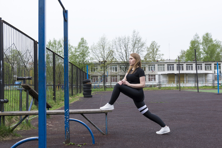 girl in black sportswear engaged in sports on the Playground outdoors,  young woman trains ,workout Reklamní fotografie - 122781178