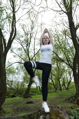 1 white girl doing yoga among the green trees, girl standing on one leg on a stone with her hands up, young woman standing in a yoga tree pose Reklamní fotografie - 122781176