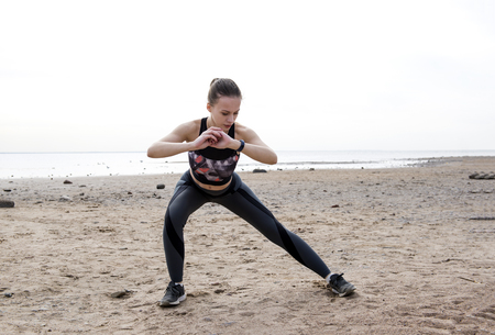 1 white slim, sporty girl in sportswear doing sports on the beach on the beach in cloudy weather,  woman doing a workout Reklamní fotografie - 122781182