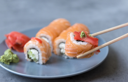 Philadelphia rolls with ginger and wasabi in sticks on a gray background, rolls with salmon, Japanese rolls on a plate Reklamní fotografie - 122781184