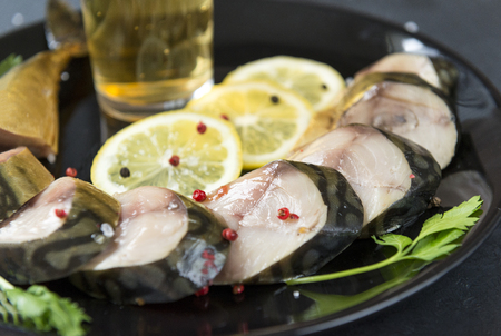 pieces of smoked mackerel with spices and parsley on a plate, lemon pieces, salted fish, snack for beer Reklamní fotografie