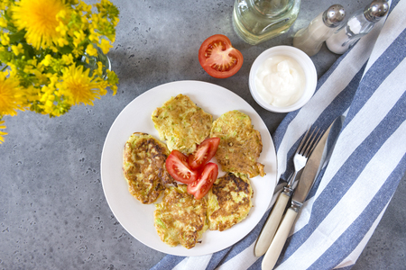 fritters of zucchini with slices of tomato on the plate, gravy boat with cream sauce,  fork,  knife, towel,  bouquet of dandelions, salt, pepper, jar of oil, top view, vegetable fritters