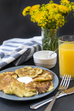 zucchini pancakes with sour cream on a plate, a glass of orange juice ,a bouquet of yellow flowers, dandelions, towel, fork ,spoon on a dark background