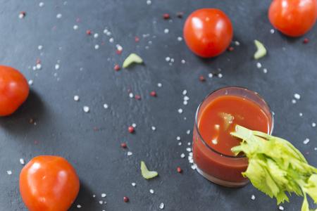 glass of fresh tomato juice with celery sprig, fresh tomatoes, salt and pepper on black surface, drink Reklamní fotografie - 122781220