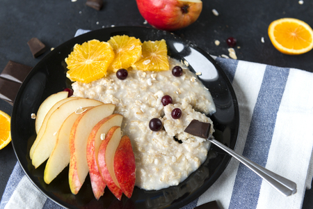 porridge with fruit pieces , cranberry berries and chocolate, oatmeal in a plate, Reklamní fotografie
