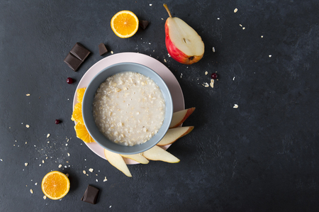 porridge, a plate of oatmeal, pieces of orange, pear, chocolate on a black background Reklamní fotografie - 122781219