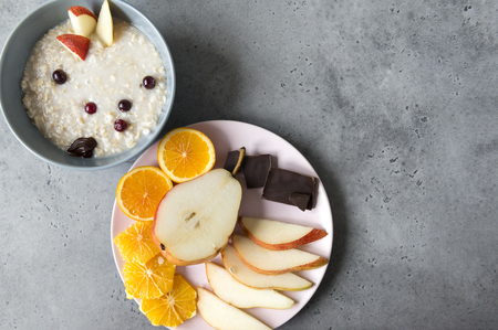 plate of porridge with berries and pieces of pear, half pear, cranberry berries, chocolate pieces, orange slices on a plate, oatmeal on a gray background Reklamní fotografie