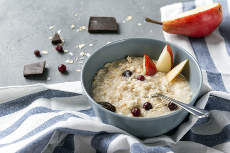 oatmeal with cranberries, pear slices, pieces of chocolate, a towel, on gray background