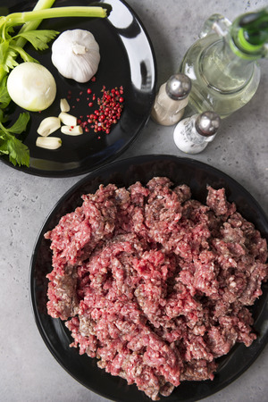 raw ground beef on a black plate, onions, garlic, celery, pepper on a plate, salt shaker, a bottle of sunflower oil, meat