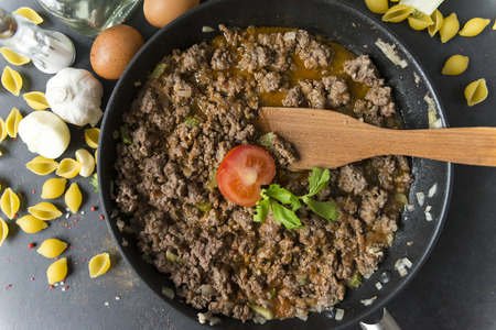 meat gravy to pasta with tomato in a pan , wooden spatula, shell paste, eggs, garlic, onion, spices, butter, top view Reklamní fotografie