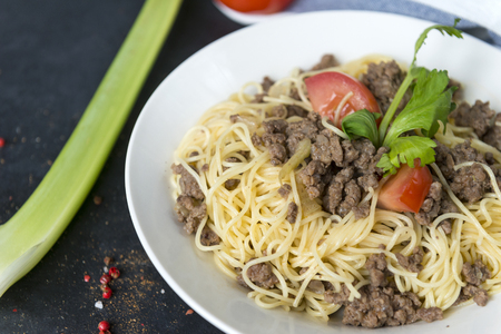 pasta with ground beef, tomato and celery on a white plate