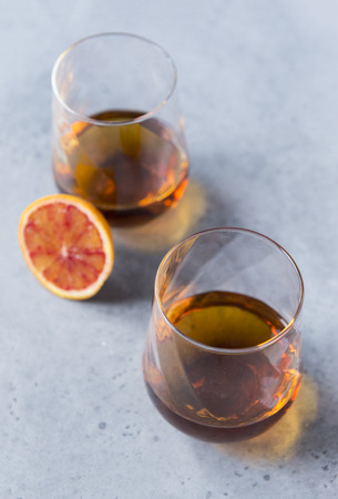 2 glasses of cognac on a gray background, a piece of orange, alcoholic drink 스톡 콘텐츠