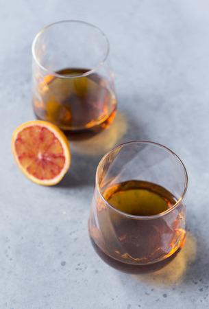 2 glasses of cognac on a gray background, a piece of orange, alcoholic drink Reklamní fotografie - 122781229