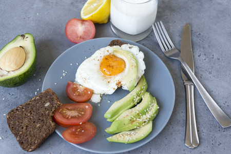 scrambled eggs, avocado slices with sesame seeds on a plate, slices of whole grain bread,  glass of milk, healthy Breakfast, tomato, lemon, fork, knife on a gray background